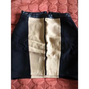Nederdel i lækkert fast materiale fra Zara, med læder-look detalje. Brugt få gange.