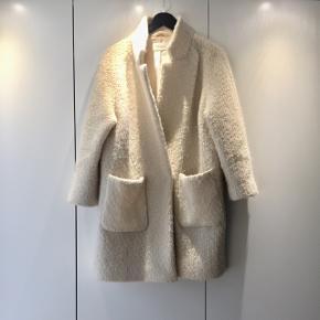 """Sælger denne populære Ganni uldfrakke/jakke, der er et par sæsoner gammel. Nyprisen var 1.999 kr.  Den har ingen pletter, eneste synlige slid er lidt uldfnuller, men da overfladen i forvejen er lidt """"ruflet"""" bemærkes det ikke. 😊   Lidt oversize i det. Jeg er str 36/s og passer denne perfekt. Kan også passes af str 38/m.   Farven er creme / beige."""