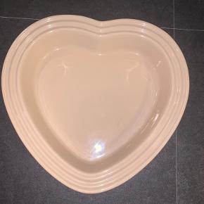 Hjerteformet fad fra Le Creuset i stentøj.  Ø 25 cm. Kan tåle frysetemperatur og varm temperatur. Tåler opvaskemaskine. Fejler intet!