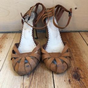Sælger disse stilletter i læder.  De trænger til en ny hæl. Selve hælen har lidt hakker.  Skoen får en gang læder pleje inden salg.