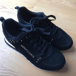 Sorte ruskinds sneakers fra Versace Det ene V mangler - og derudover er der brugsridser på guldkanten bagerst på skoen - se billeder. Ellers fin stand.