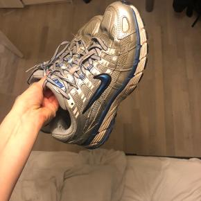 Pænt slidte Nike p-6000 i grå og blå  De brugt en del gange derfor lidt hul ved halen som jeg dog ikke synes mærkes når man går med dem  De sælges rigtig billigt men der stadig mange gode km i dem og de kan sagtens vaske for blive mere rene