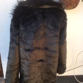 Meget blød imiteret pels. Den lukkes med hægter Brystmålet er 2 x 66 cm Længden er 85 cm