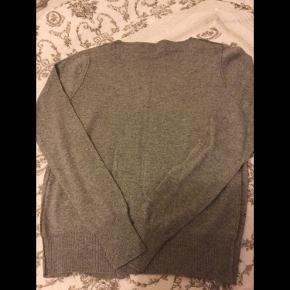 Flot og blød grå strik cardigan med stjerne detaljer fra Paris, aldrig brugt str S/M, lækker blød kvalitet, har tryk knapper, er som ny.  Pris 125 kr + porto