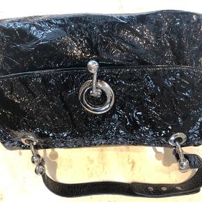 Flot laklædertaske med massiv sølvbesætning.  Fremstår som ny.  Tekstilfoer. Indvendig lynlåslomme.  Skulderstrop medfølger.  Mobiltelefon-lomme og andet rum.  Magnetlås.  Mål:  25x 30g 18 cm Prisen er fast. Sendes til køber.