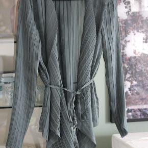 Silkebluse fra rosemunde, farven er en blanding af petroleums-grågrøn. Har brugt blusen to gange og folk er vilde med den, men jeg kommer vist aldrig til at kunne bruge silke. Slå-om/wrap bluse med smukke plisseringer i stoffet.