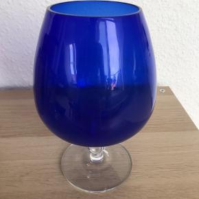 Smukt stort blåt krystalglas med klar fod. Har et lille afslag under foden.  Kan bruges til lys eller andet dekoration. Mål: h: 20cm ø: 13cm