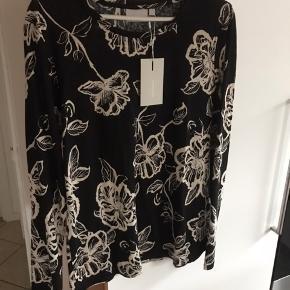 Flot sort bluse med mønster den er ny med tags og aldrig brugt kun prøvet sælges kun da jeg har tabt mig meget så den ikke passer mig 😊😊