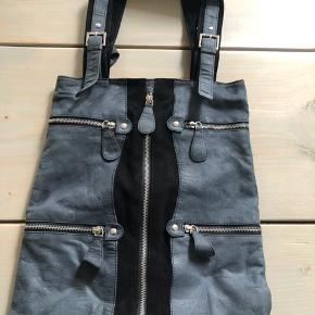 Taske i kombineret blå/grå læder og sort ruskind med fine detaljer af chrom lynlåse.  Lynlås-rum indeni tasken.  Måler: 40 x 35 cm. (Uden hank)  Aldrig brugt.