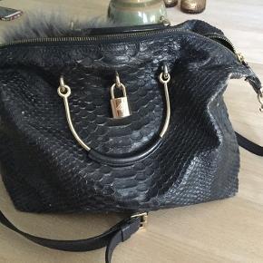 Tasken er brugt men i god stand. Den trænger til fedtstof. Farven hedder ink blue og er næsten sort.