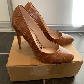 Flotte stiletter fra Mango i modellen Rosa. De er lavet af lysebrunt, croc inspireret syntetisk læder. Indersiden af skoen og sålen mener jeg er ægte læder. Skoene er aldrig brugt, kun prøvet på. Kommer fra ikke-ryger hjem.  Hælhøjde: 10 cm  Køber betaler fragten, hvis ikke vi mødes og handler. Jeg sender med DAO.