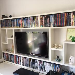 """Byd gerne. Bytter gerne med en sovesofa med chaiselong eller et større garderobeskab  Hjemmebygget tv- og dvd-møbel inkl. vægbeslag til 32"""" fladskærm. 181x105x14  Dette væghængte tv-møbel er perfekt til filmelskeren og/eller i små lejligheder. Har plads til 32"""" væghængt tv i midten og masser af dvd'er og nipsting. Møblet er hjemmebygget, men ikke af mig, så jeg kan ikke oplyse om materialer. Derfor har møblet også en del 'charme' med lidt skæve vinkler og mål, men det er ikke noget man lægger mærke til (se f.eks. hvordan pladen buer lidt op over tv'et). Desuden kunne det trænge til et nyt lag maling, da det har småskrammer rundt omkring, men det er generelt velholdt.  Vær opmærksom på, at møblet er tungt, og derfor ikke kan hænge på tynde vægge. Tv-vægbeslag med arm (bevæges ud og drejer til siderne) kan medfølge.  Kan evt. leveres i Århus i starten af august"""