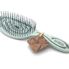 Lime green NORDIC BIO BRUSH  En hårbørste produceret på bioplast i form af sukkerrør og korn.  Børstehovedets loopdesign gør den yders fleksibel og at den nænsomt gi'r efter og følger hovedbunden med sin kurvede design.   Piggene er designet til at gribe meget hår og er skånsomme.