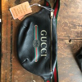 Den flotteste bæltetaske fra Gucci i den store model. Den fremstår uden brugsspor og standen er i top. Jeg har desværre aldrig selv brugt den, så den fremstår i samme stand, som da jeg modtog den! Den er i det lækreste skind og som ny - og modellen kan stadig fås i butikkerne. Den er oprindeligt en herremodel, men vil mene, at den er unisex. Den er købt på Vestiaire og derfor medfølger der ægthedsbevis og dustbag fra Vestaire, samt den kasse, den er sendt i.  Obs: Ved lynlåsen inde i foret, er der en lille misfarvning i det lyse for, der ellers fremstår i super stand. Den står pt. til 7300kr online. Prisen er ikke fast og jeg modtager gerne realistiske bud, fra jer der har en oprigtig interesse i en fantastisk taske til en kanon pris!