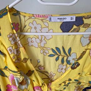 Mango Bluse i gul med blomster og flæser.  Str. L, men lille i størrelsen. Vaskemærke er klippet af, vaskes ved 30 gr. Let bomulds stof.  Brugt få gange og fejler intet.   Kan sendes mod at køber betaler 🌸