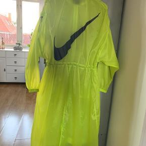 Letvægter jakke fra Nike i neon gul med sorte detaljer og rynkebånd over skuldre og i taljen.