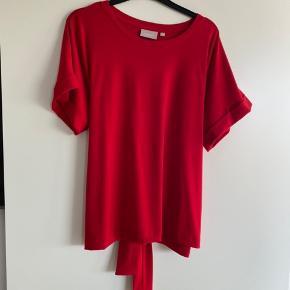 Lækker blød bluse med fastsyet opsmøg på det korte ærme. Bindebånd, der kan bindes både foran eller bagpå efter ønske. Giver en flot silhuet, når det er bundet.