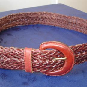 Varetype: Rødbrunt flettet læderbælte 85 X 4 cm Størrelse: 85 X 4 cm Farve: Rødbrunt  Flettet, rødbrunt læderbælte størrelse 85 gange 4 cm. Brugt et par gange og fremstår i flot stand. BYTTER IKKE!