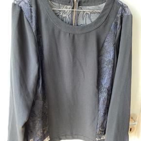 Sort bluse med blå blonder i siderne og på ryggen.