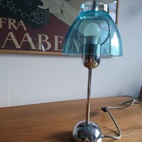 Fed bordlampe i sølv stel med blå lampeskærm.