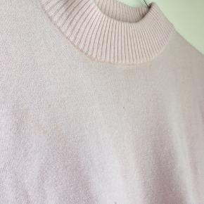 Oversized, lyserød t-shirt sweater, lille mærke på brystet. Har dog ikke prøvet at vaske den, så kan måske godt komme af