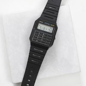 Casio CA53W-1 calculator Ur  Indbygget lommeregner +- gange og dividere Vand resistant Stopur måling ned til 1/100 af et sekund, op til 23:59'59.99, med flere funktioner Automatisk kalender Vejer 29g Dual time, kan holde øje med to tidszoner på samme tid Brugt meget få gange Kond 9/10
