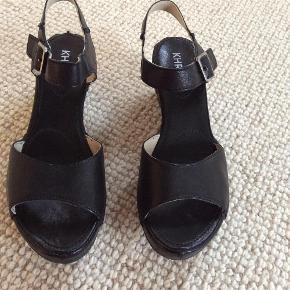 Varetype: Sandaler Farve: Sorte Oprindelig købspris: 1000 kr.  KHRIO Smukke sandaler,  Sorte, Flot hæl, Rem over foden, som kan indstilles efter foden. Haft dem på en eneste gang. Flotte...BYD...som NYE.