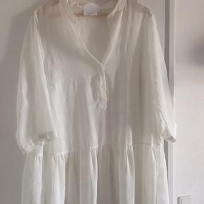 Let, luftig og transparent tunika fra Zizzi sælges. Den har trekvartlange ærmer, knapper halvvejs ned foran og flæser forneden.