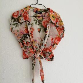 Blomstret skjorte som bindes om maven