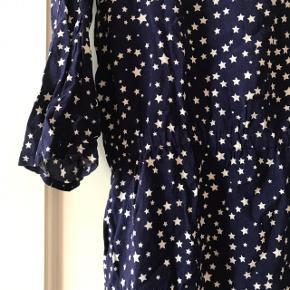 Skøn mørkeblå kjole fra H&M med hvide stjerner på ⭐️⭐️ kjolen er str. 40. Den er brugt få gange, men har dog fået en løbet tråd bagpå omkring numsen 🙈 ellers rigtig pæn stand med elastik i taljen og 2/3 ærmer.   Bemærk - Sendes med DAO (37 kr), bytter ikke og sender ikke billeder med varen på ⭐️☺️
