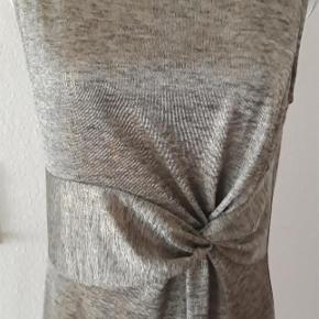 Brand: Anna Field Varetype: Selskabs  eller sommerkjole Farve: gold/grå Oprindelig købspris: 349 kr. Prisen angivet er inklusiv forsendelse.  Enkel , sommer eller selskabskjole.  Kjolen er lidt i facon syet , er glat, er lidt elastisk , har pæn behagelig underkjole .  Farve er grå/ guld som danner pæn nuancer .   Kjolen er lavet af 95 % polyester , 5 % elasthan ,  Brystmål - 84 cm  Længde målt bagfra - 92 cm  Ny , aldrig brugt