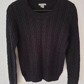Kabelstrikket trøje fra H&M i sort, ribkant i halsudskæring, ved ærmer og forneden.  Den er hverken falmet på mave eller ryg, som det ligner på billederne - beklager det dårlige lys.  Køber betaler forsendelsen.