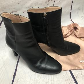 This Prada black leather ankle boot has a classic look. It is slim fitting, but comfortable as the heel is solid. Round toe.