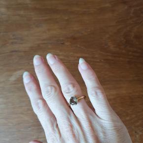 Forgyldt ring med facetslebet sten af røgkvarts. Mærke: Carré Copenhagen Jewellery.  Carré og 925 står præget inde i ringen.  Diameter (indvendig mål): 16 mm. Størrelse på sten fra kant til kant: 8 mm. Brugt 2 gange. Ingen slid.  Prisen er fast og rimelig i forhold til markedsprisen.  Kan afhentes i Esbjerg eller sendes på købers regning og ansvar.