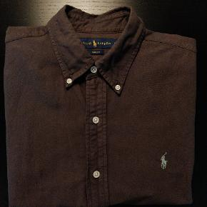 """Brun Oxford skjorte fra Polo Ralph Lauren i slimfit. Brugt 4-5 gange, men denne model er """"prewashed"""" or den fremkommer derfor som ny og er helt uden slid eller skader."""