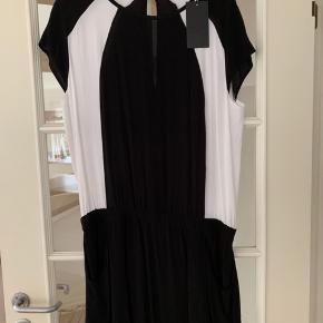 Super lækker kjole i sort og hvid med elastik i taljen. Skirtet har lommer i siderne. Lukkes i nakken med en knap. Kvalitet: 100% Viskose