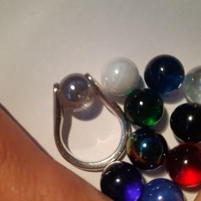 """Rigtig flot """"Magic ring"""" m ti udskiftelige sten/perler, der gør det muligt at matche alle farver af outfits. Ringen er brugt lidt og har små fine """"brugs ridser"""" ( se billede ). Diameter ca 1.8 cm - målt ml de lukkede sider. Prisen incl de ti udskiftelige """"kugler"""" er ca kr 1000 -, Er klar på evt bud, da ringen er blevet for stor."""