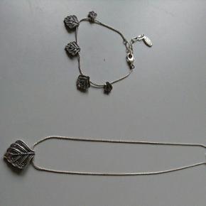 Smykkesæt fra Pilgrim bestående af halskæde og armbånd. Det er små blade med små sten i enderne.