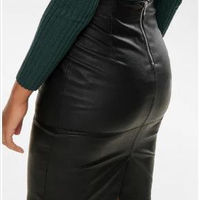 Imiteret ledernederdel. Lækker følelse når man rører ved materialet og har nederdelen på. Lynlås bagpå.