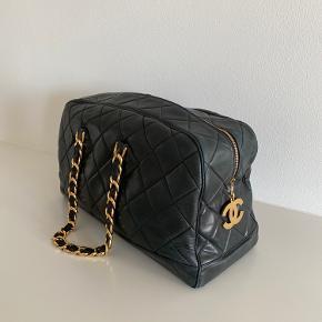 """Super flot og lækker Chanel weekendtaske i meget mørk navy (syner sort).  Den er fra 1992 og taget i betragtning, hvor mange år den har på bagen, er den i flot stand. Der er brugspor- primært på hjørnerne, og det er der taget højde for i prisen. Den har """"dutter"""" under bunden som tager det værste slitage.   Den er endnu flottere i virkeligheden!! :-) Den ville have godt af en gang læder conditioner 😊 Jeg vil kalde den sort, men officielt er den navy.  Se billeder - der er flere i kommentarerne.   Mål: ca. 25 x 48 x 22  Befinder sig i Aarhus."""