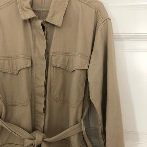 Beige denim jakke med bindebånd i talje fra Pieces. Fitter 36-38, størrelse 40 kan også passe, her vil den være mindre oversized. Ingen tegn på slid.