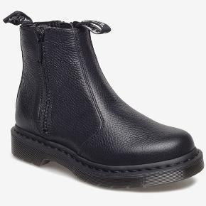 Helt nye Dr. Martens støvler (2976 W/Zips Black Milled Nappa). Støvlerne har aldrig været brugt og fremstår derfor som helt nye uden brugsspor. Almindelig pasform. Kom med et bud!