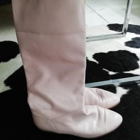 Skind. 80er look. Kanten kan foldes ned så støvlen bliver kortere. Beige indvendig farve. Slidt indvendigt og fnugger. Det kan ikke ses når støvlen ikke er foldet.