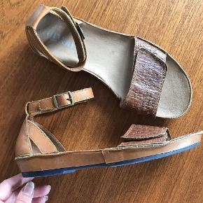Varetype: Lækre flade sandaler med ankelrem / læder Farve: brun / cognac  Lædersandaler med fast hælkappe og ankelrem, der lukkes med velcro (snydespænde). Sandalerne har ligeledes velcro i stykket, der løber hen over foden, hvilket giver mulighed for at justere bredden en smule.  Kun brugt en enkelt gang, så super fine.  Indvendig sållængde: ca. 25,5 cm
