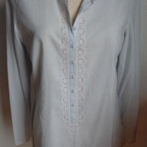 Varetype: Flot skjorte m. hulmønsterbroderi Farve: Lys blå  Flot skjorte med smuk detalje med hulmønsterbroderi og fine små knapper. Der står 40 i, men den passe nok bedst af 38. Er brugt en enkelt gang. Porto er beregnet med DAO