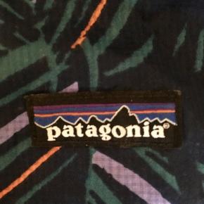 Letvægtsjakke fra Patagonia. Den er regn og vindtæt, og så kan den pakkes så meget sammen, at den ikke fylder mere end en tændstiksæske. Brugt meget få gange :-)