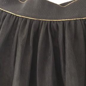 Tyl nederdel med elastik i talje brugt en gang aldrig vasket   Smuk sort Co'couture maxi-nederdel med elastikkant i gulglimmer og guldkant. Nederdelen har 2 lag a gennemsigtigt tyl, som giver et elegant look med foer indenunder.  Yderstof: 100% Polyester Foer: 100% Viskose Skånevask ved 40 grader