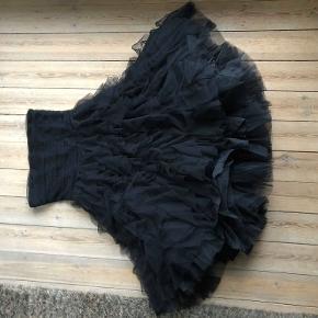 Fantastisk tylkjole med corsage. Perfekt til galla eller nytår.  Kjolen er bygget op af flere lag tyl.  Kjolen har lynlås i siden og holdes oppe med en gummikant i corsagens kant.  Der har fulgt stropper med, men de er desværre forsvundet. Det anbefales derfor, at man har en barm, der kan fylde kjolen ud (hvilket jeg ikke har).  Kun brugt én gang.  Mål: Længde: ca. 104 cm. lang fra top til kant.  Bredde (corsage): ca. 42 cm.  Kjolen er lavet af 100% tyl og 100% acetate.  Kjolen er derfor let at pakke sammen og fylder ikke så meget.