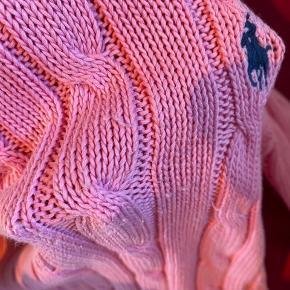 """Fin strik fra Ralph Lauren i pink. Dette er en small fra børneafdelingen, men er selv en small og kan sagtens passe den. Den er som beskrevet brugt meget og har derfor også """"fnuller"""" og tråde der er gået lidt op diverse steder. Dette er dog ikke noget man tydeligt lægger mærke til, og den kan sagtens bruges."""