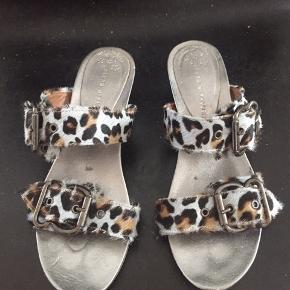 Super seje og feminine sandaler fra spanske Pierre Mirailles i pels (skind). Bundfarven er nærmest gråblå, kombineret med brun og sort. Lædersåler.   Brugt nogle gange sidste sommer, det kan ses på sålerne, ellers i fin stand. Lidt små i størrelsen.  Jeg kan ikke huske nypris, men det var over 1000 kr.